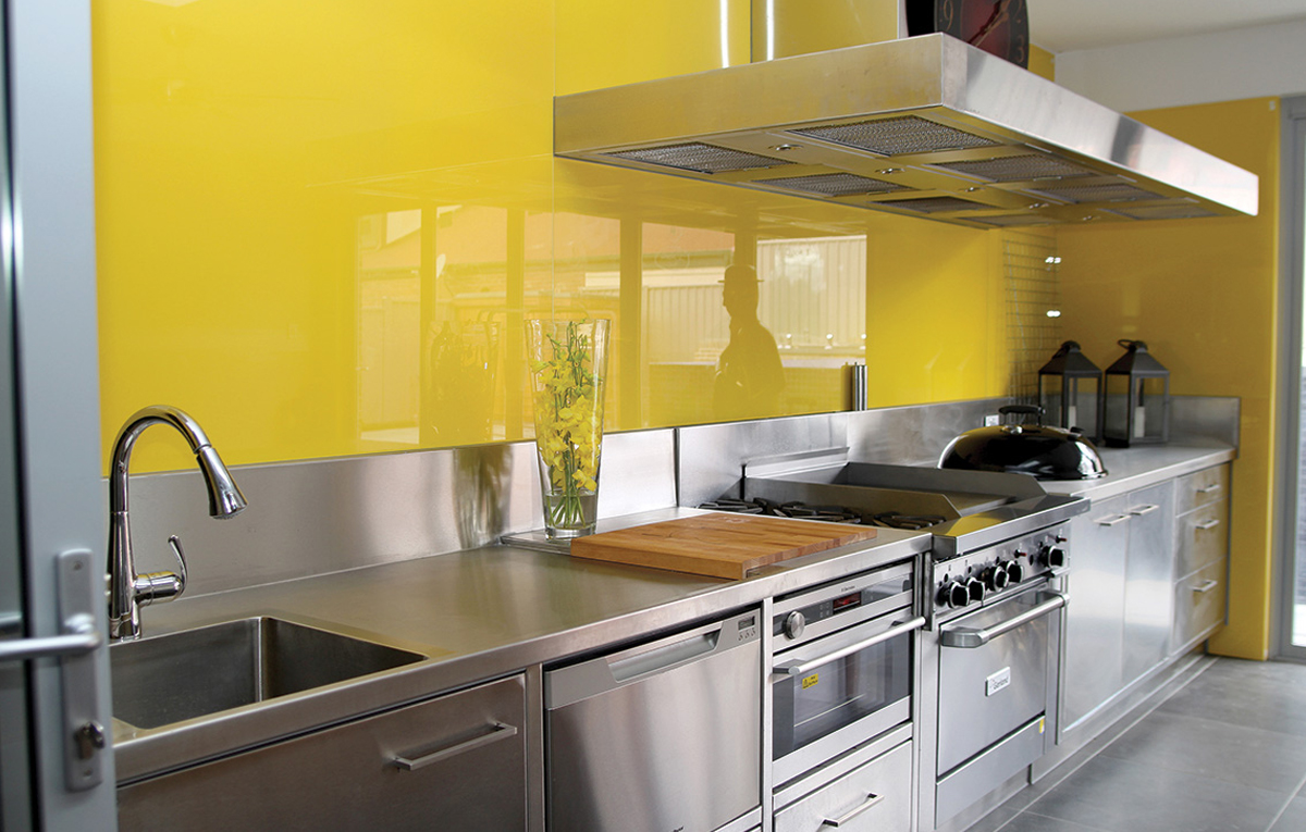 Yellow glass splashback in kitchen.